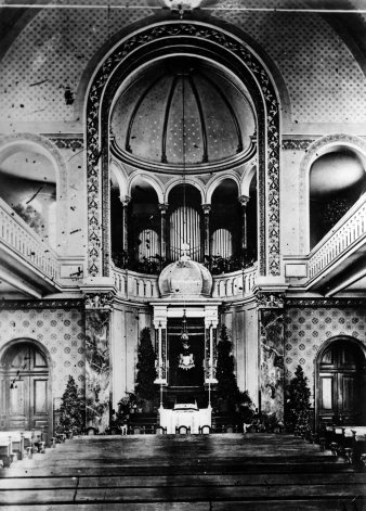 Black and white photograph of the interior of a synagogue, with Torah shrine, benches and circular gallery