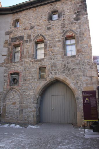 North facade of the Old Synagogue. The bricked-up former entrance door, to the right of it a large entrance gate from the time of conversion into a storehouse, which serves as the entrance today.
