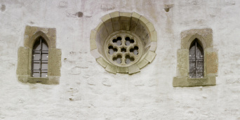 Detail of the facade. A large rose window is flanked by two smaller lancet windows.