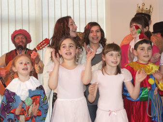 Dressed-up children, singing and clapping their hands