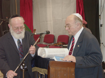 Two men wearing kippas at a lectern