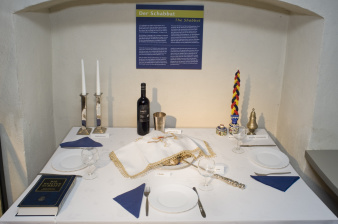 Festively laid table with three plates, cutlery, wine glasses, a bottle of wine and candles in the background