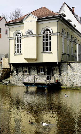 Facade of the Small Synagogue facing the river. Large, narrow windows with round arch.