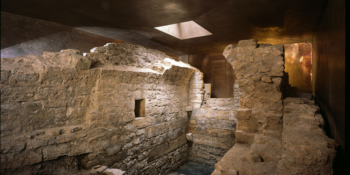Parts of the walls of the medieval mikveh. Remains of a small vaulted cellar room, surrounded by its bronze-coloured protective building.