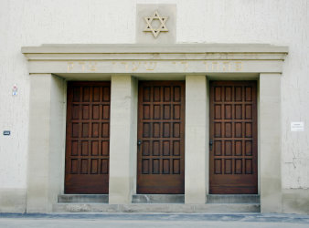 Three wooden doors in a row, lined with pillars, above the Star of David