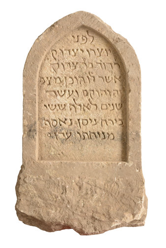 The picture shows a Jewish gravestone from the Middle Ages. It is made of light-coloured sandstone and bears a Hebrew inscription.