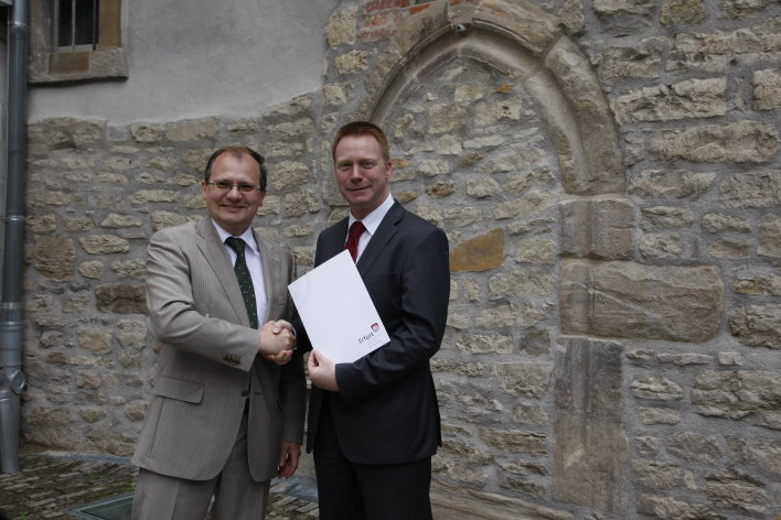 In front of the Old Synagogue's northern facade, the Deputy Mayor for Construction and Traffic, Mr. Ingo Mlejnek, submits the Statement of Outstanding Universal Value to the Thuringian Minister for Education, Science and Culture, Mr. Christoph Matschie.
