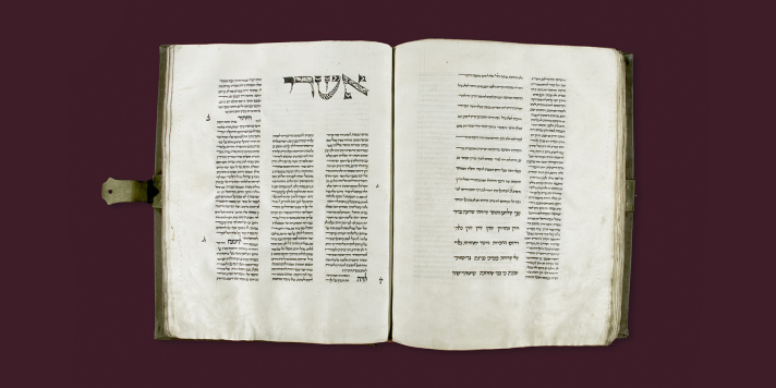 Double page of a medieval hebrew manuscript. Several columns of text and a large ornamented initial on the top of the left page.